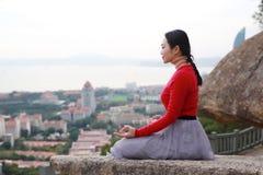 瑜伽妇女在凝思姿势坐山峰岩石 免版税库存图片