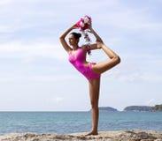 瑜伽妇女在海滩摆在桃红色的海附近 免版税库存图片