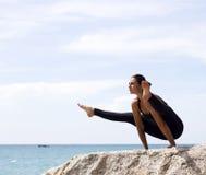 瑜伽妇女在海滩摆在海和岩石附近 免版税库存图片