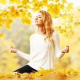 瑜伽妇女在秋天公园 库存照片