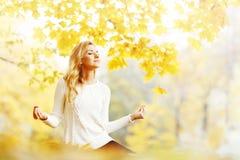 瑜伽妇女在秋天公园 库存图片