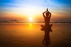 瑜伽妇女坐沿海在日落 旅行 免版税库存图片