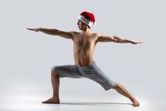 瑜伽姿势战士2在圣诞老人帽子 图库摄影