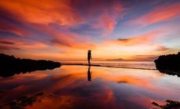 瑜伽姿势的一名妇女现出轮廓反对与她的反射的日落在水2中 免版税库存照片