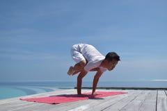 瑜伽姿势的亚裔中国妇女由海 免版税库存照片