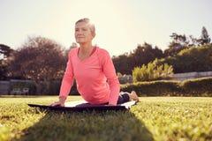 瑜伽姿势的健康资深妇女与柔和的sunflare 免版税库存图片