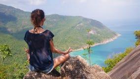 瑜伽姿势的女孩有海岛的美丽如画的看法在高度 库存图片