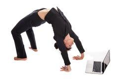 瑜伽姿势的适合的妇女与膝上型计算机一起使用。 库存照片