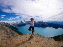 瑜伽姿势的适合的妇女在高山湖包围与雪加盖的山 免版税库存照片