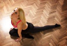 瑜伽姿势的金发碧眼的女人在地板上 免版税图库摄影