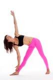 瑜伽姿势的-三角位置俏丽的妇女。 免版税库存照片