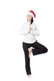 瑜伽姿势的年轻办公室妇女在白色后面的圣诞老人帽子 免版税库存图片