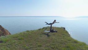 瑜伽实践、信奉瑜伽者坚强男人和灵活的妇女在海洋附近执行山的被配对的平衡的锻炼户外 股票录像