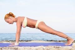 瑜伽实践-亭亭玉立的妇女实践的板条姿势 库存照片