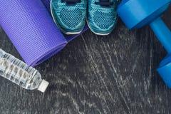 瑜伽席子、体育鞋子、哑铃和瓶在蓝色背景的水 概念健康生活方式、体育和饮食 体育equipmen 免版税库存图片