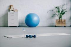 瑜伽席子、哑铃、塑料瓶水和健身球在客厅 库存照片