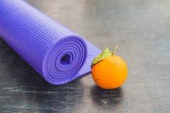 瑜伽席子、水、桔子和芒果在木背景 瑜伽的设备 概念健康生活方式、饮食和体育 复制Spac 库存图片