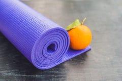 瑜伽席子、水、桔子和芒果在木背景 瑜伽的设备 概念健康生活方式、饮食和体育 复制Spac 图库摄影