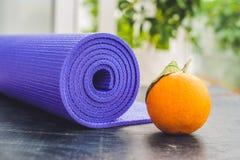 瑜伽席子、水、桔子和芒果在木背景 瑜伽的设备 概念健康生活方式、饮食和体育 复制Spac 免版税库存照片