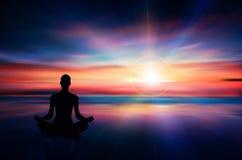 瑜伽思考在日落五颜六色的天空的妇女剪影 图库摄影