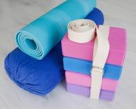 瑜伽扶植块、皮带、路辗和地毯 免版税库存照片