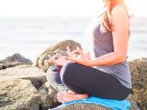 瑜伽概念 在海滩的特写镜头妇女手实践的莲花姿势在日落 免版税库存照片