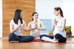 瑜伽的孕妇在健身演播室把坐舒展胳膊的席子分类 免版税图库摄影