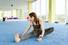 瑜伽的时刻 可爱的年轻女人行使和坐在健身房的地板 r 库存照片