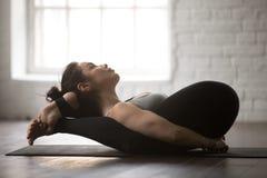 瑜伽的睡眠姿势的年轻可爱的妇女,白色顶楼演播室 库存照片