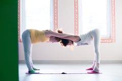 瑜伽类的怀孕的少妇室内与辅导员协助 库存照片