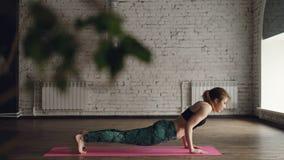 瑜伽老师展示站立在大轻的演播室的中心的asanas复合体明亮的席子的 妇女是 影视素材