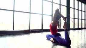 瑜伽舒展臀部,腿筋的席子妇女干涉,有鸽子姿势舒展的腿肌肉 20s白种人女孩做 影视素材