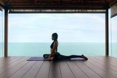 瑜伽训练 体育的妇女给舒展身体穿衣在海附近 免版税库存照片