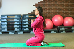 瑜伽训练 一套桃红色体育衣服的美丽的白女孩在瑜伽类思考在健身中心 库存图片