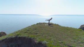 瑜伽锻炼、坚强的信奉瑜伽者男人和灵活的妇女执行acroyoga被配对的平衡的锻炼本质上在山的 股票视频