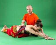 瑜伽 辅导员帮助妇女执行asana 免版税库存照片
