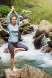瑜伽asana Vrikshasana树姿势的妇女在户外瀑布 免版税库存照片