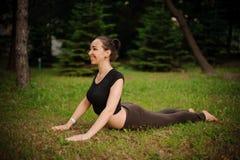 瑜伽bhujangasana由妇女的眼镜蛇姿势绿草的在公园 免版税库存图片