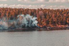 瑞典斯德哥尔摩群岛,来自火的烟做温暖在村庄之外的冷的热水锅 库存图片