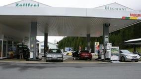 瑞士人和旅客人填装油对汽车坦克在加油站的在村庄 股票录像