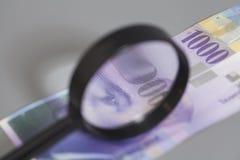 瑞士人在放大镜下的1000法郎钞票 库存图片