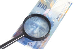 瑞士人在放大镜下的100法郎钞票 免版税库存图片
