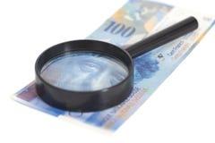 瑞士人在放大镜下的100法郎钞票 库存照片