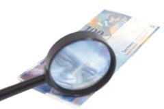 瑞士人在放大镜下的100法郎钞票 库存图片