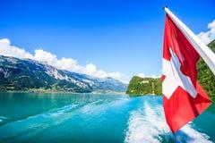 瑞士国旗在巡航小船` s尾端有瑞士自然阿尔卑斯、湖和蓝天背景美好的夏天视图  免版税图库摄影