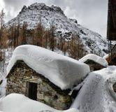 瑞士山中的牧人小屋的屋顶cowred与雪 免版税库存图片