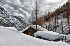 瑞士山中的牧人小屋的屋顶cowred与雪 图库摄影