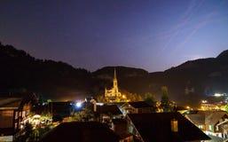 瑞士村庄在与房子的晚上和窗口点燃和高山教会在中心 免版税图库摄影
