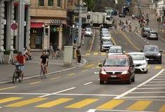 瑞士苏黎士- 2017年6月03日:自行车骑士和汽车在stre 免版税库存图片