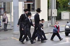 瑞士:走横跨街道的正统犹太人民 库存图片